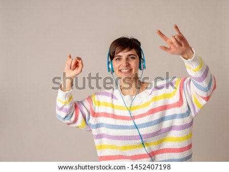 Portrait of gorgeous and happy brunette woman in colorful striped jumper listening music in headphones singing and dancing on neutral background. In positive emotions, youth and happiness concept. #1452407198