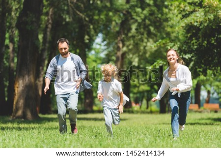 happy family running in park during daytime and looking at camera #1452414134