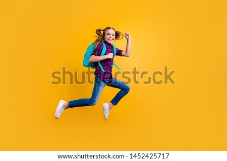 Full length side photo of little pupil jump high glad return school wear casual checkered shirt jeans denim isolated yellow background #1452425717