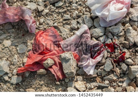 Dirty, old, bloody rags thrown away on the abandoned gravel road  #1452435449
