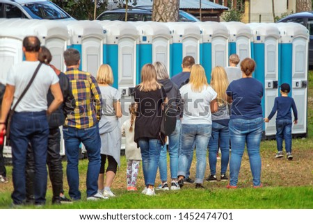 Group of people standing near portable toilets in a park #1452474701