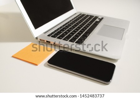 Laptop and telephone on an infinite white background with notes pots #1452483737