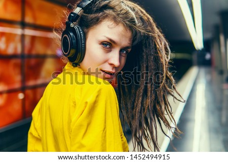 Beautiful young girl with purple pink hair listening to music on headphones, street style, outdoor portrait, hipster girl, music, mp3, Bali, beauty woman, sunglasses, orange color, concept,underground #1452494915