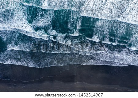 Aerial drone view of Atlantic ocean waves washing black basaltic sand beach, Iceland Royalty-Free Stock Photo #1452514907
