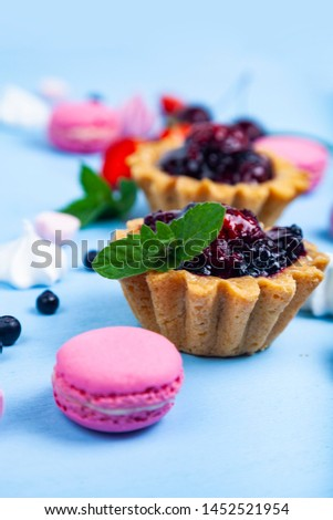 Small berry cake and ripe berries on a blue wooden background. Delicious dessert. #1452521954