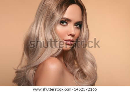 Ombre blond wavy hairstyle. Beauty fashion blonde woman portrait. Beautiful girl model with makeup, long healthy hair style posing isolated on studio beige background. #1452572165