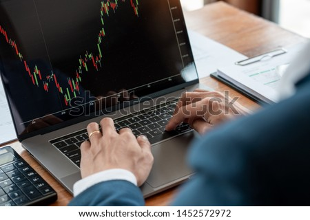 businessman or broker looking at computer laptop analysing about stock market invest trading stocks graph analysis candle line in office room. #1452572972
