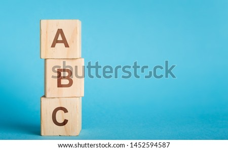 School begginnings. ABC letters of wooden blocks in pillar form on blue background, copy space #1452594587