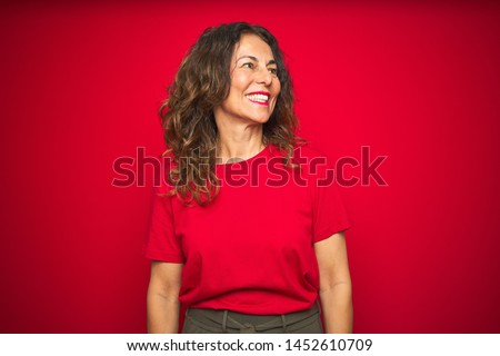 Middle age senior woman with curly hair over red isolated background looking away to side with smile on face, natural expression. Laughing confident. #1452610709