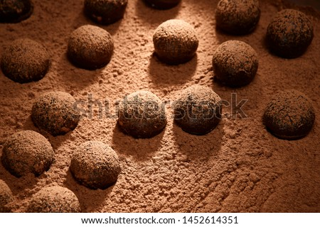 Bitter chocolate brigadeiros getting chocolate powder layer #1452614351