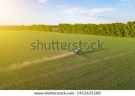 Aerial view of a farm tractor in a green field during spraying and irrigation with pesticides and toxins for growing food, vegetables and fruits on summer sunny day. Agriculture industry. #1452635180