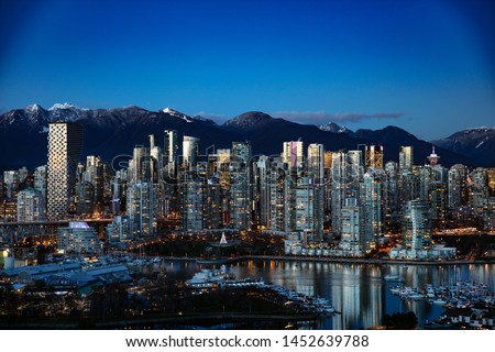 Vancouver Cityscape that shows the famous and recently built Vancouver House framed with snow-capped North Shore Mountains