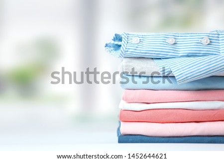 Multicolored stack of clothes,colorful coton loundry folded empty space background.Laundry. Royalty-Free Stock Photo #1452644621