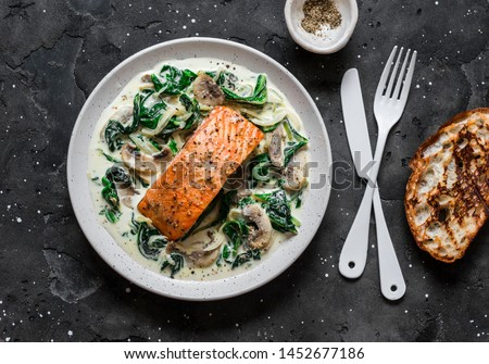 Baked salmon with creamy spinach mushrooms sauce on a dark background, top view. Salmon florentine #1452677186