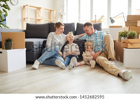 Group of positive young family in casual outfits sitting on floor and leaning on sofa while getting settled in new home #1452682595
