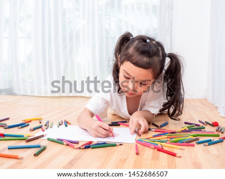 Asian little cute girl lying on the floor and use color pencil drawing cartoon on white paper. Preschool lovely kid with  drawing at paper near the window. Learning and education of kid.