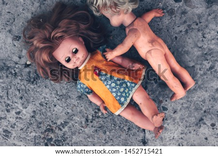 Two old dirty plastic dolls hugging on a concrete floor. Discarded old things. The concept of a bygone childhood #1452715421