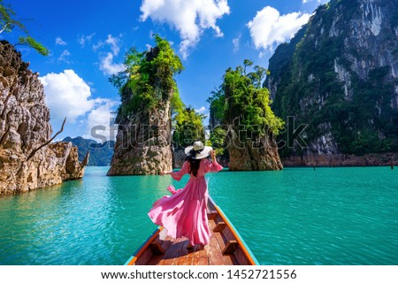 Beautiful girl standing on the boat and looking to mountains in Ratchaprapha Dam at Khao Sok National Park, Surat Thani Province, Thailand. #1452721556