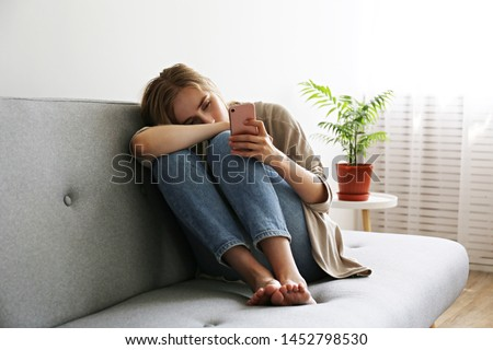 Portrait of beautiful young woman with depressed facial expression sitting on grey textile couch holding her phone. Cyber bullying victim concept. Sad female in her room. Background, copy space. #1452798530