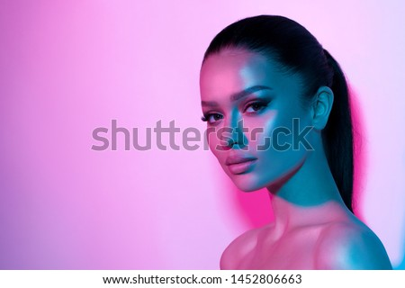 High fashion model woman's face in colorful bright neon UV blue and purple lights. Beautiful girl posing in the Studio, glowing makeup, colorful makeup. Glitter bright neon makeup.  #1452806663
