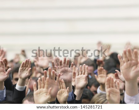 Closeup of business crowd raising hands Royalty-Free Stock Photo #145281721