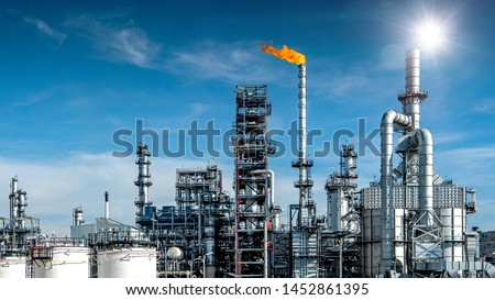 Close-up view Oil and gas industrial refinery zone,Detail of equipment oil pipeline steel with valve from large oil storage tank at cloudy sky. -image #1452861395
