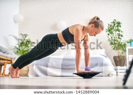 woman doing exercise on a special simulator balancer. blonde athletic sportswear, home did exercise strengthens the muscles. the girl keeps her balance balancing on the sports equipment.copy space. #1452889004