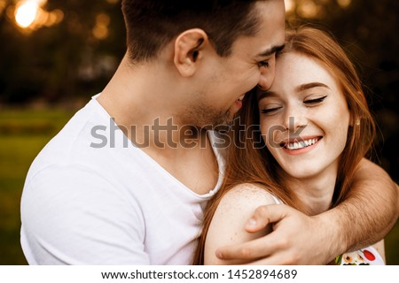 Amazing close up portrait of a cheerful caucasian red haired woman with freckles laughing with closed eyes while embracing with her man against sunset outside. #1452894689