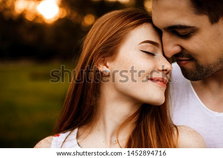 Close up side view portrait of a amazing couple embracing closely with closed eyes smiling against sunset outside while dating. #1452894716