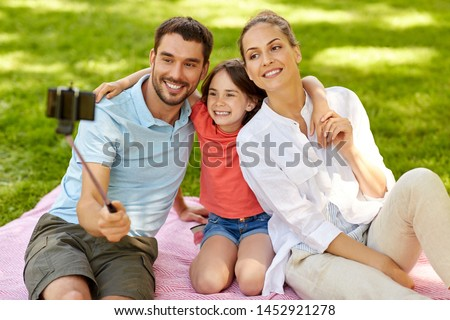 family, leisure and technology concept - happy mother, father and daughter having picnic and taking picture by smartphone on selfie stick at summer park #1452921278
