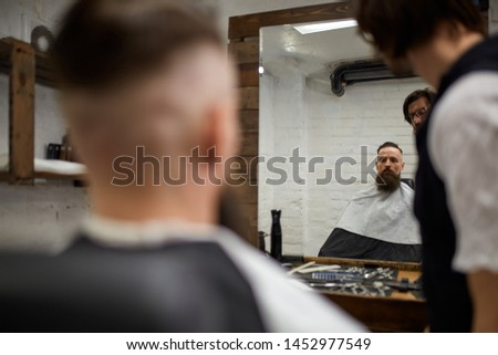 Brutal guy in modern Barber Shop. Hairdresser makes hairstyle a man with a long beard. Master hairdresser does hairstyle with hair clipper #1452977549