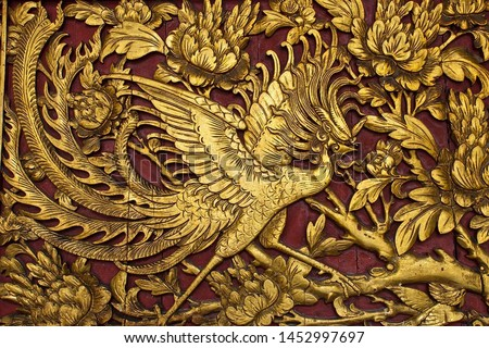 Beautiful golden chinese phoenix bird engraved with gold on the wall of Nankunshen Daitian Temple.