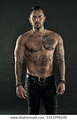 Brutal strict macho with tattoos. Masculinity and brutality. Tattoo culture concept. Tattoo brutal attribute. Man brutal unshaven hispanic appearance tattooed arms. Bearded man show tattooed torso. #1452998240