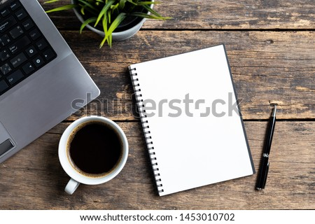 empty notebook with coffee and computer on wooden table ,top view Royalty-Free Stock Photo #1453010702