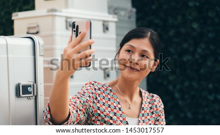 Asia woman using smartphone in front of large luggage #1453017557