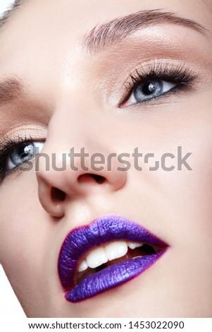 Closeup macro shot of human woman face. Female with natural eyes makeup and bright violet lips #1453022090