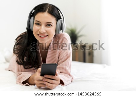 Beautiful young woman relaxing listening to music with  headphones on bed at home #1453024565