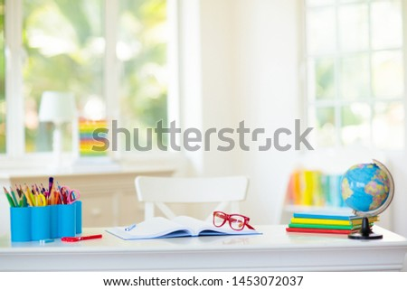 Back to school. Kids bedroom with wooden desk, books, globe, backpack, glasses and pencils. White room with big window for young child. Home interior for girl or boy. Table for homework and study. #1453072037