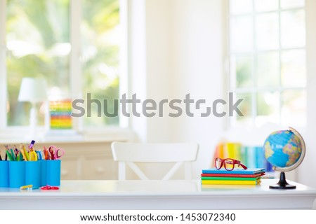 Back to school. Kids bedroom with wooden desk, books, globe, backpack, glasses and pencils. White room with big window for young child. Home interior for girl or boy. Table for homework and study. #1453072340