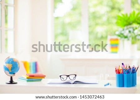 Back to school. Kids bedroom with wooden desk, books, globe, backpack, glasses and pencils. White room with big window for young child. Home interior for girl or boy. Table for homework and study. #1453072463