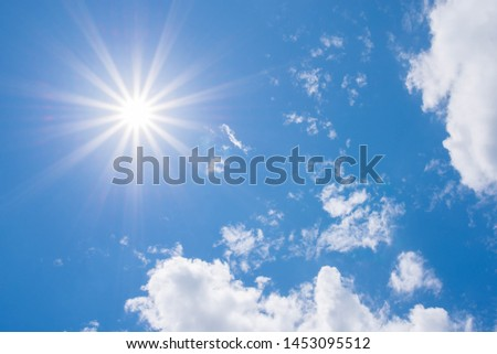 Beautiful Sunny Sky Background with White Clouds. Shining Sun at Clear Blue Sky. Summer Background with Sunlight and Clouds on Blue Sky.
