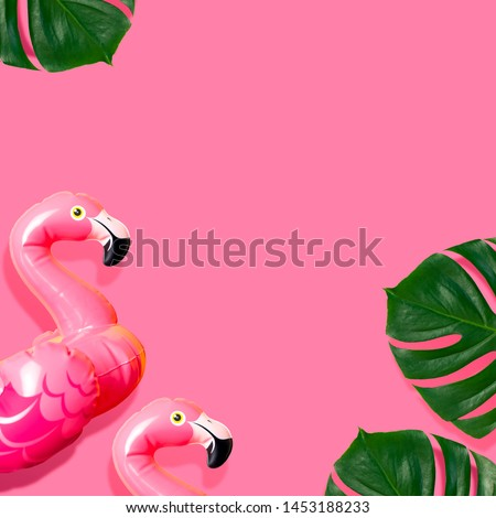 Creative summer beach concept. Inflatable pink mini flamingo and tropical leaf monstera on pink background, pool float party. Flat lay copy space. Flamingo Trend Inflatable Toy. Summer background