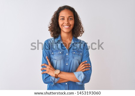 Young brazilian woman wearing denim shirt standing over isolated white background happy face smiling with crossed arms looking at the camera. Positive person. #1453193060