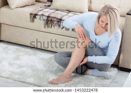 Middle-aged woman suffering from pain in leg at home, closeup. Physical injury concept. Ankle pain, painful point. #1453222478