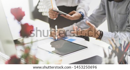 Team of business analysts discussing the business strategy in contemporary office room with blurred background  #1453250696