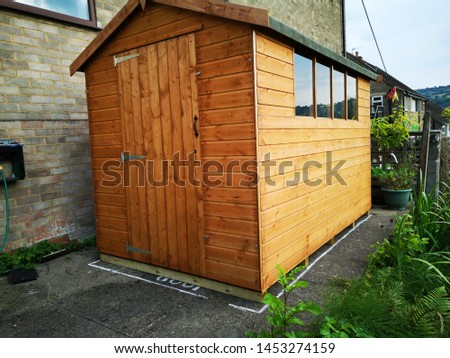 A heavy duty untreated wooden garden shed with windows and an apex felt roof #1453274159