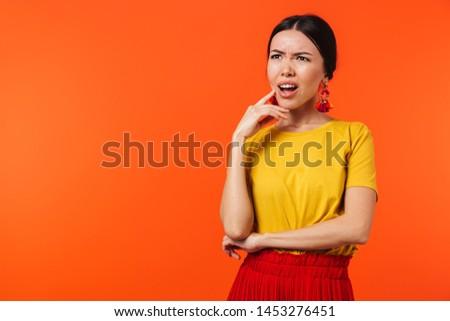 Image of a beautiful confused displeased young woman posing isolated over orange wall background. #1453276451