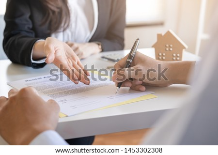 Salesmen are letting the male customers sign the sales contract, Asian women and men are doing business in the office, Business concept and contract signing #1453302308
