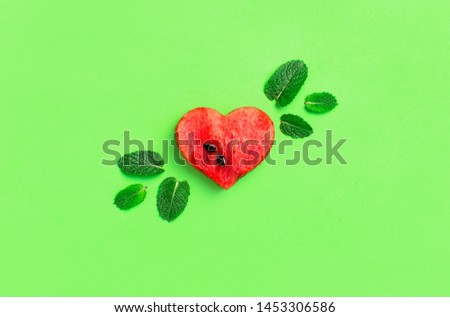 Creative summer food concept. Juicy slices of ripe red watermelon in the shape of a heart and mint leaves on green background. Flat lay, top view, copy space. Watermelon pattern. Love for watermelon  #1453306586