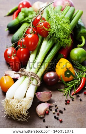 fresh spring onions and vegetables on a wooden board #145331071